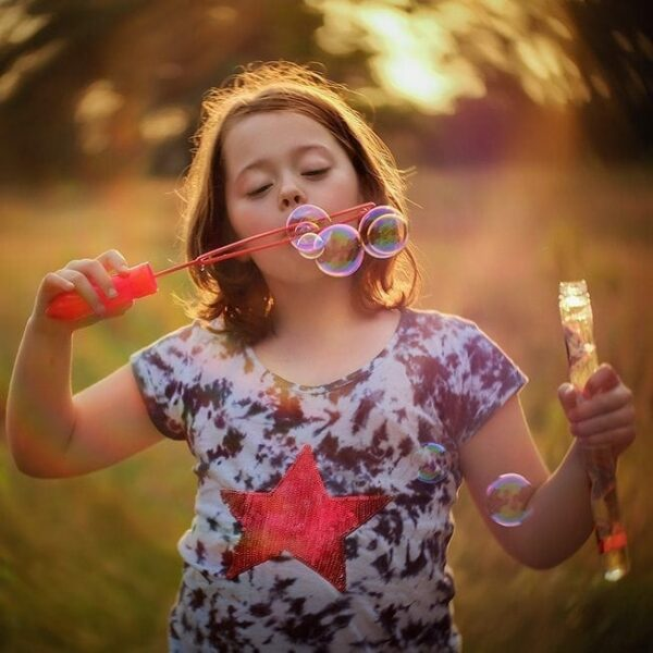 fujifilm Lensbaby twist image of a girl blowing bubbles by Willie Kers