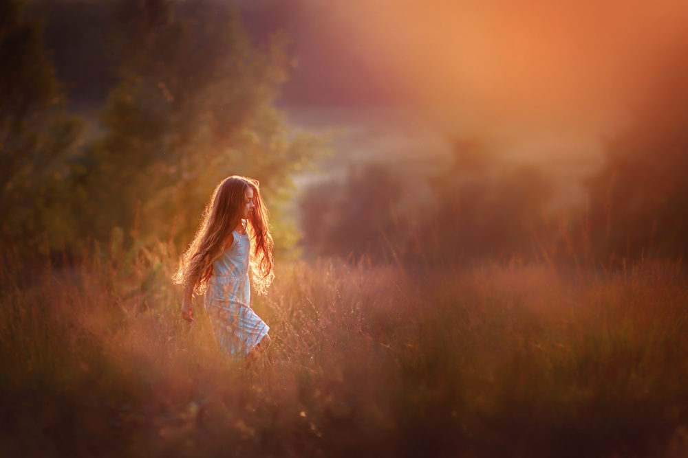 golden hour image of a girl walking through the fields by Willie Kers