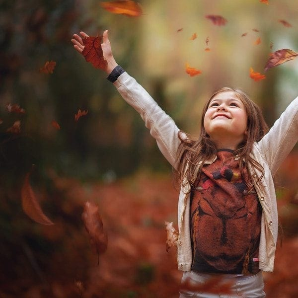 image of a girl throwing autumn leaves by Willie Kers