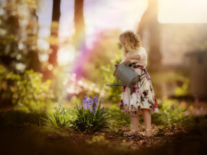 Canon EOS R portrait of a young curly girl watering spring flowers in the forest by Willie Kers photography