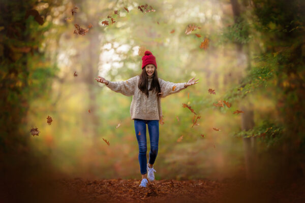 canon fine art autumn image of a very happy senior girl with a red hat throwing leaves in a magical forest by Willie Kers