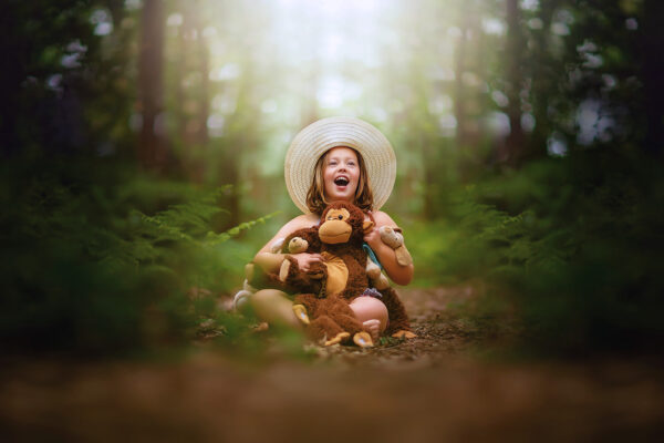 dreamy image of a child laughin in the forest with a teddy bear by Willie Kers of GlamourKidz Photography in the Netherlands dutch