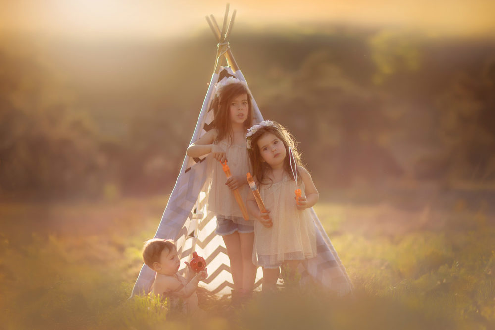 Canon color portrait of three little sisters standing in front of a tipi in sunset by Willie Kers