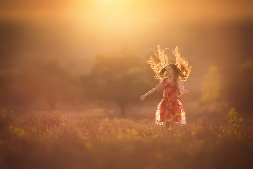 Canon sunset portrait of a childhood girl sunbathing in the open field with a pink sky by Willie Kers