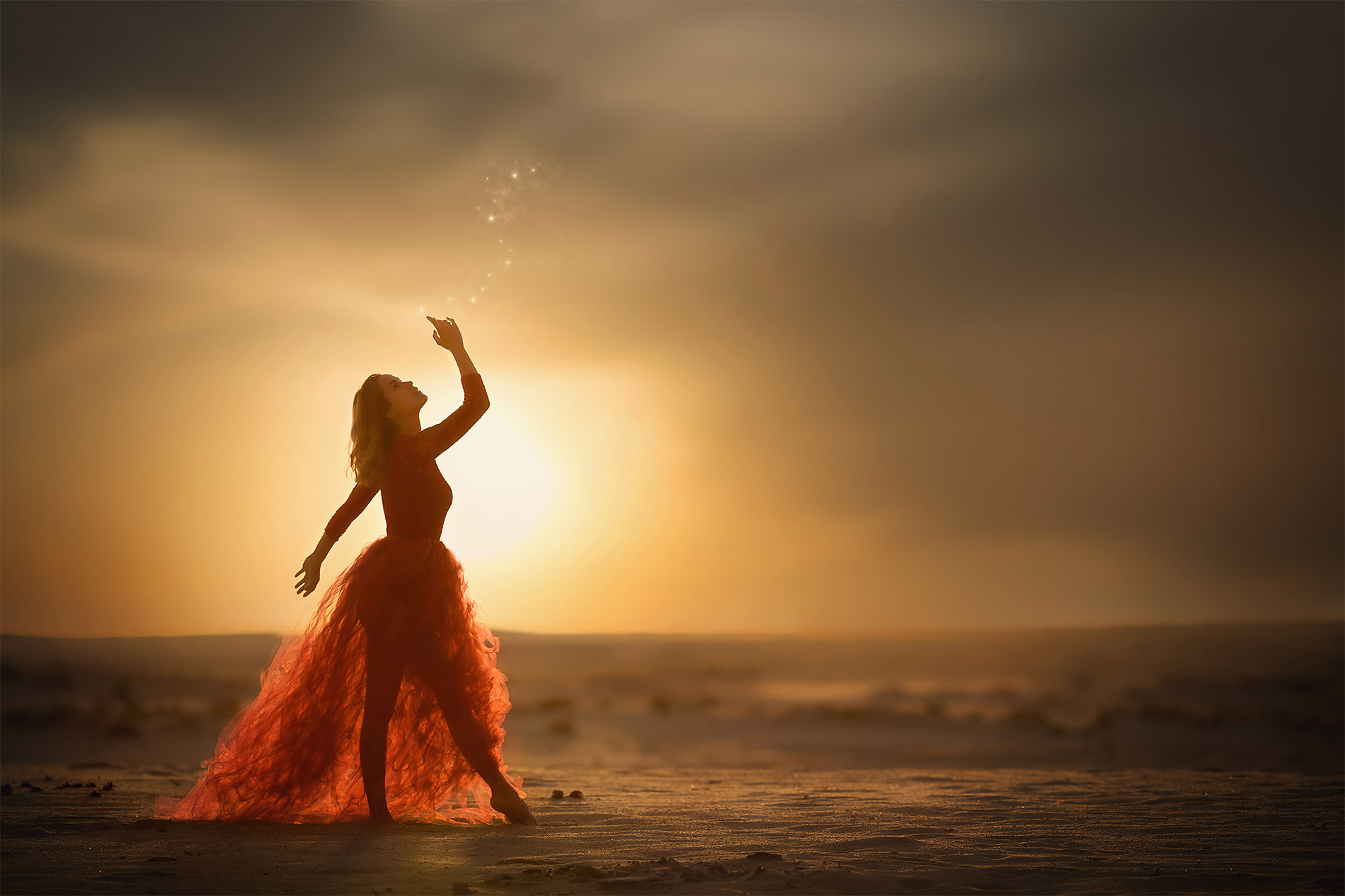 Dreamy canon image of a woman dressed up like a fairy in a red dress playing with magic fire flies in the desert during sunset by Willie Kers copy