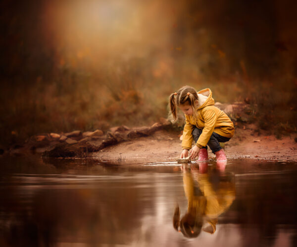 Canon Eos r6 fall image of a little girl playing with a paper boat in water wearing a yellow raincoat by Dutch photographer Willie Kers copy