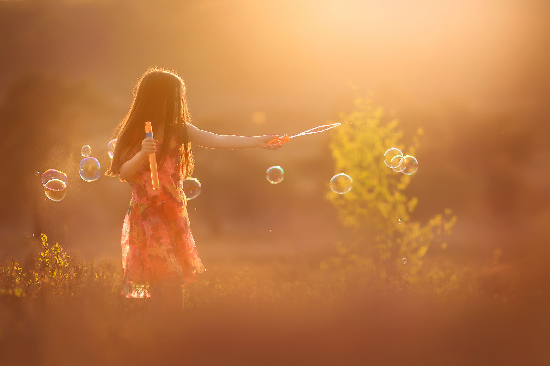 Canon color portrait of a little girl with long dark hair blowing bubbles during sunset in nature by Willie Kers