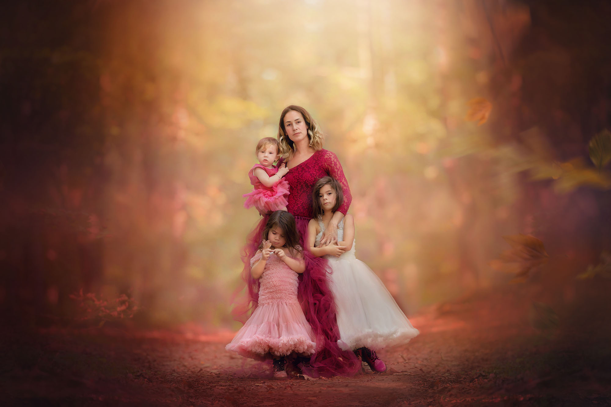 Canon 5d colorful fine art fall image of a mother and her three daughters standing in beautiful dresses in an autumn entchanted forest by Willie Kers
