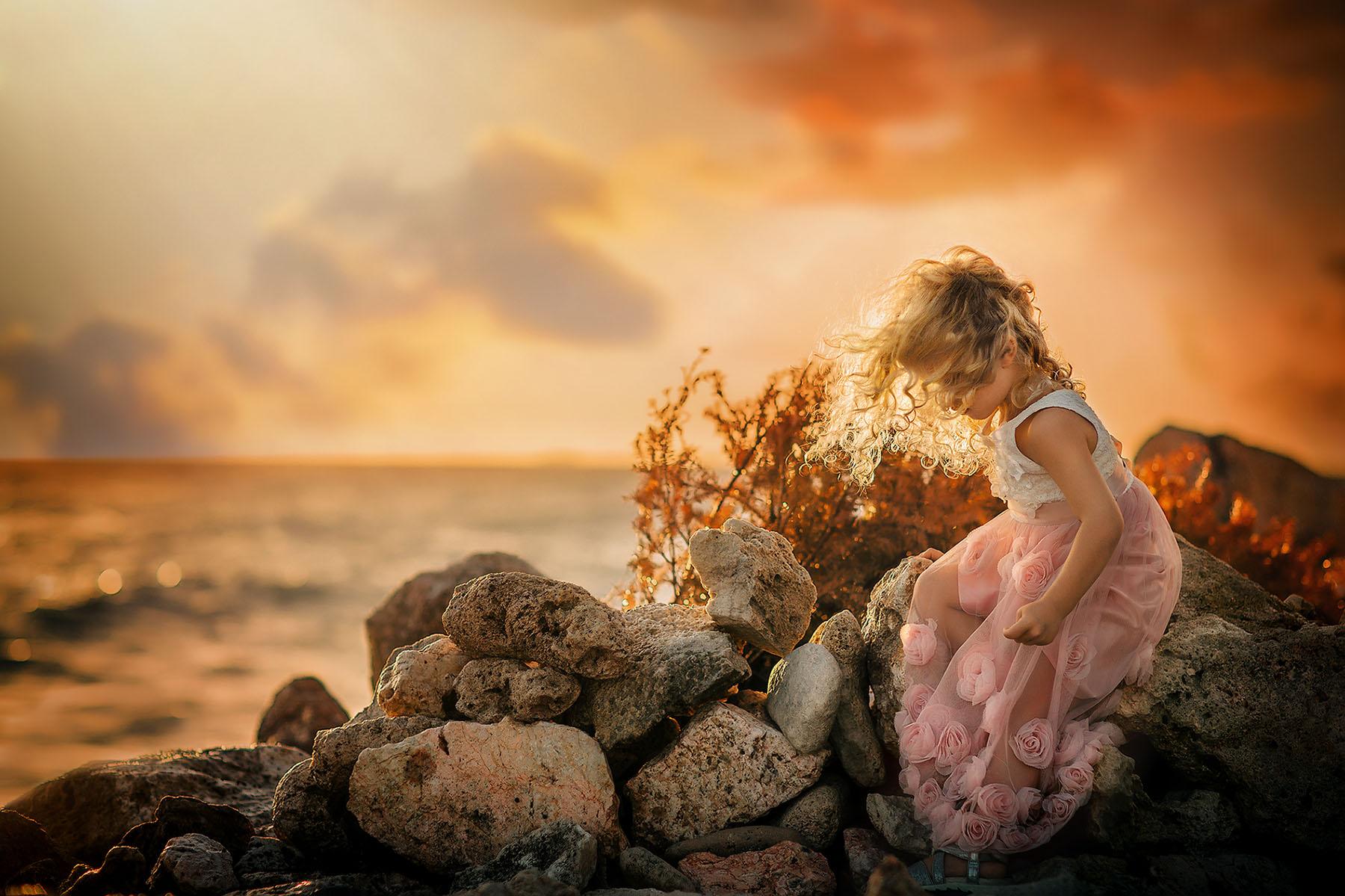 Fine art Canon Golden hour portret voor de fotografie opleiding the masters of color and light van een klein meisje met blond krullend haar zittend op de rotsen op het strand van willemstad in Curacao door Willie Kers