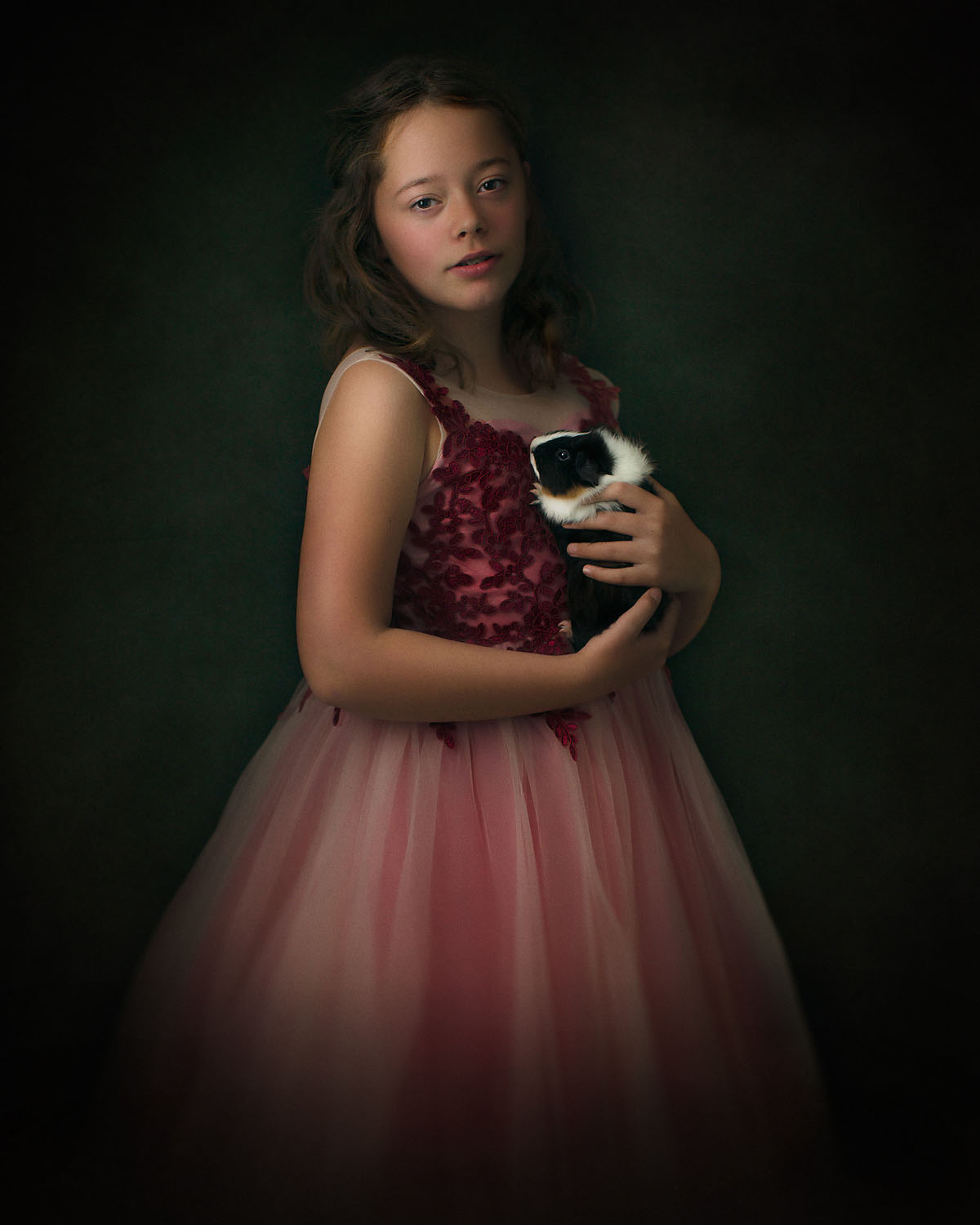 Fine art Rembrandt portrait of a young woman in a red dress holding a Guinee pig shot with profoto and canon eos R by Willie Kers
