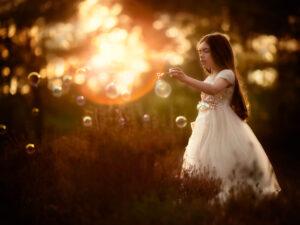 Fine art portret van een meisje in een prinsessenjurk die tijdens zonsondergang bellen blaast in het bos door portretfotograaf met natuurlijk licht Willie Kers uit Apeldoorn