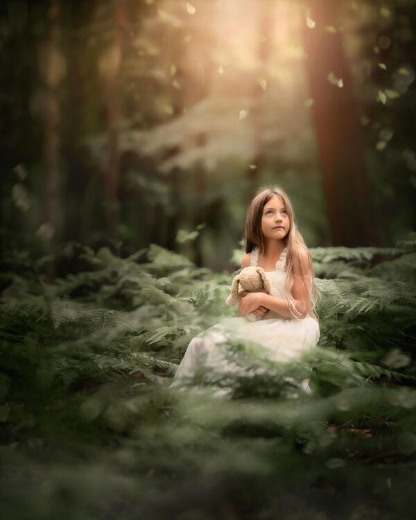 fine art portret van een klein blond meisje met een knuffel tussen de varens tijdens de natuurlijk licht fotografie workshop over de magie van het licht door apeldoornse fotograaf Willie Kers